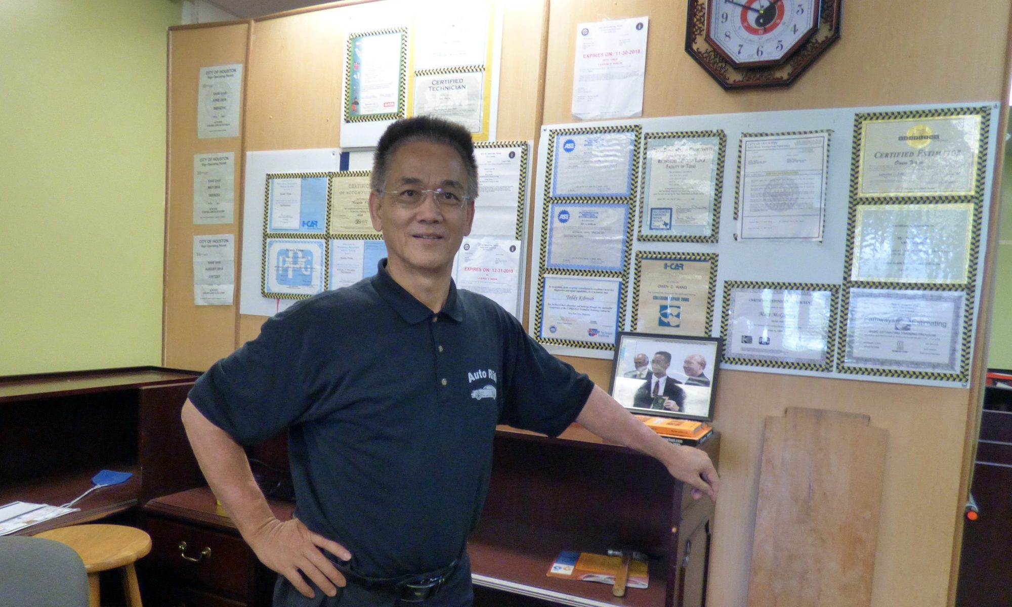 Owner - Owen Wang in front of certifications